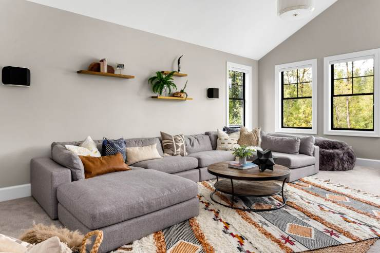 a stylish living room complete with sectional couch, large rug, and coffee table