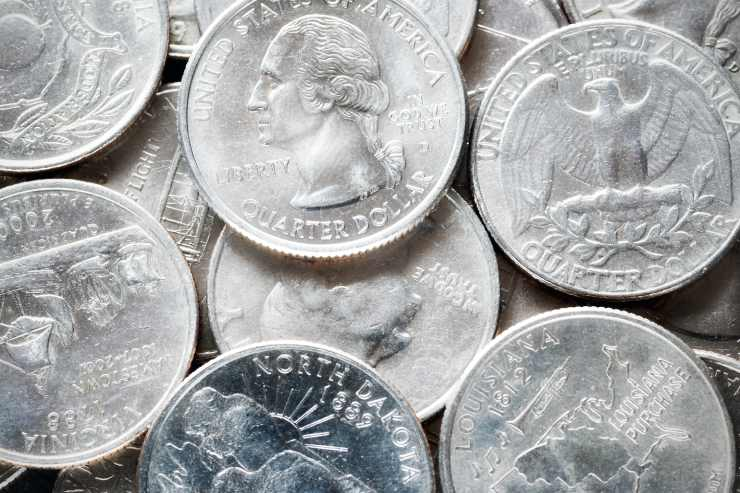 a close-up of a group of American silver quarter dollar coins