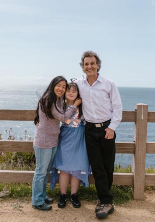 A smiling family standing in front of a fence by the shore