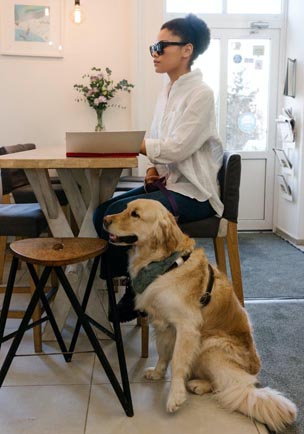A women sitting at a table with a guide dog beside her.