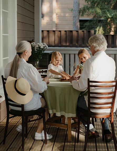 A family sitting at a table on a porch