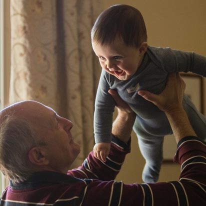 A grandfather holds up a smiling baby