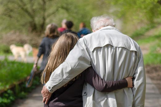 Two people walking with their backs to the camera walk down a path with their arms around each other.