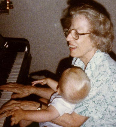 True Link co-founder and CEO, Kai Stinchcombe, as a baby in 1983, sits in his grandmother's lap as she plays a piano.