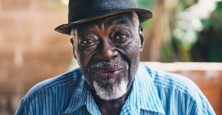 A older man with a hat smiles while looking into the camera