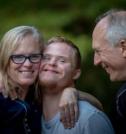 A mother and her son have their arms around each other, smiling, while the father looks looks on.