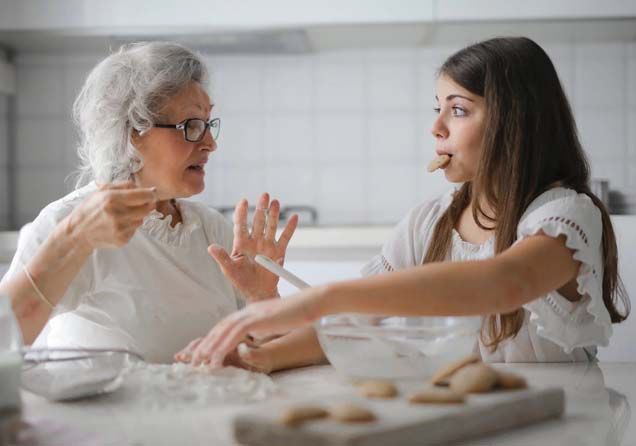 Two women making cookies and talking.