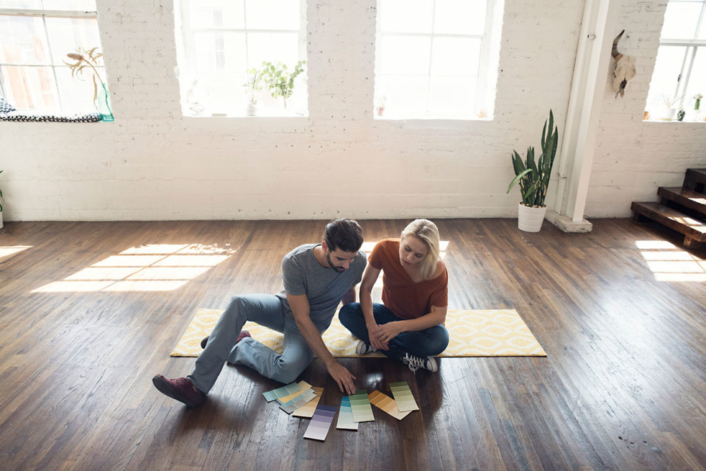 Young homeowners sitting on carpet in a loft looking at color samples