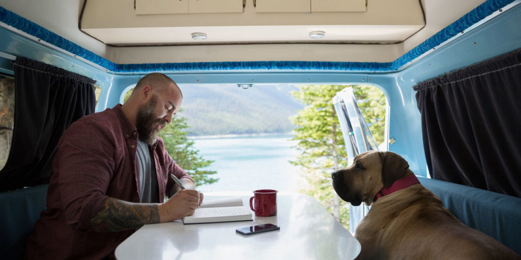 Man with dog writing in journal at table in the back of camper van at lakeside