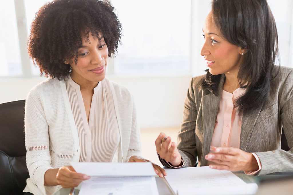 African American tax preparer consulting with a African American businesswoman
