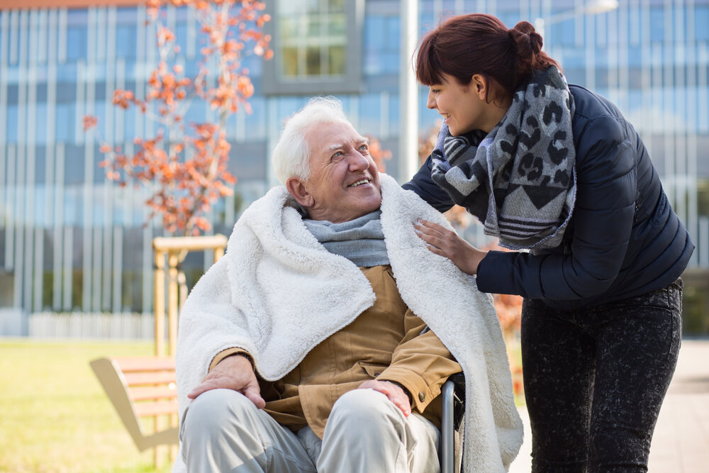 A woman wrapping a blanket around a man in a wheelchair