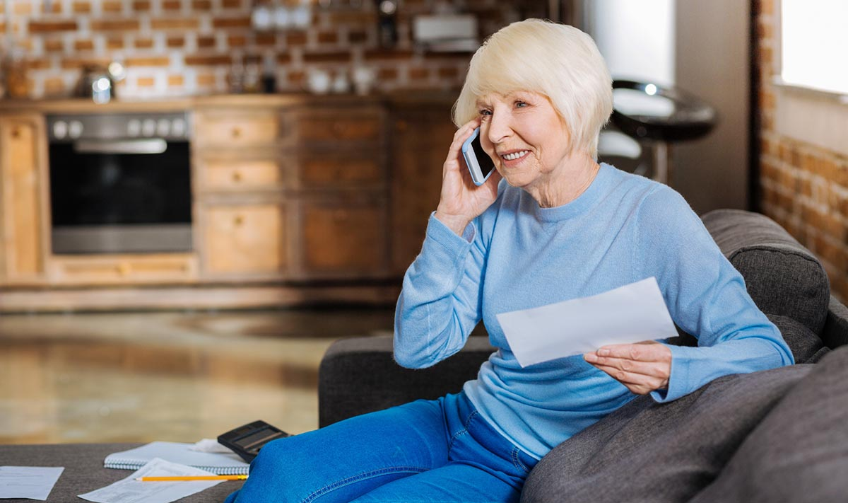 A woman talks on a phone while holding a piece of paper