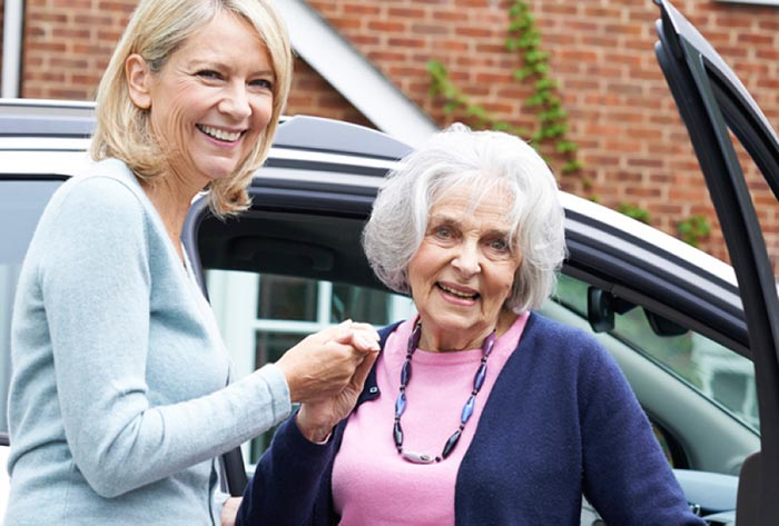 A woman helps an older woman out of a car