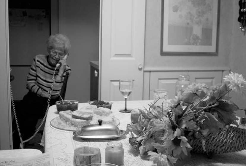 A woman on a corded phone in front of a holiday table