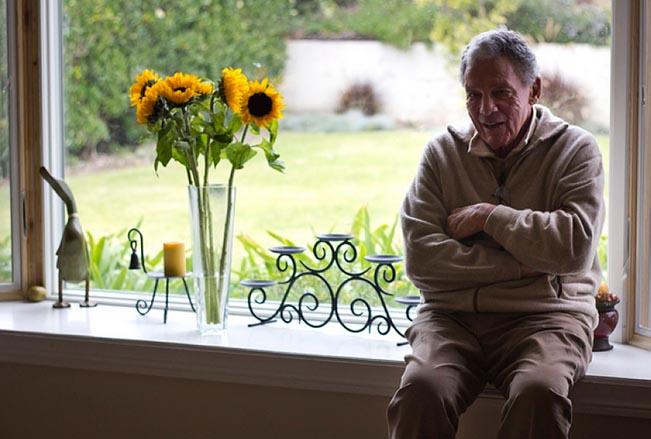 A man sits on a window sill