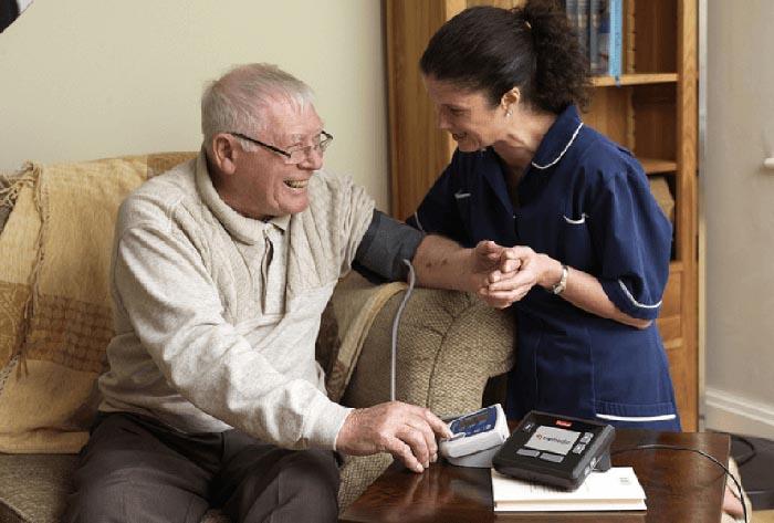 A caregiver checks a man's blood pressure