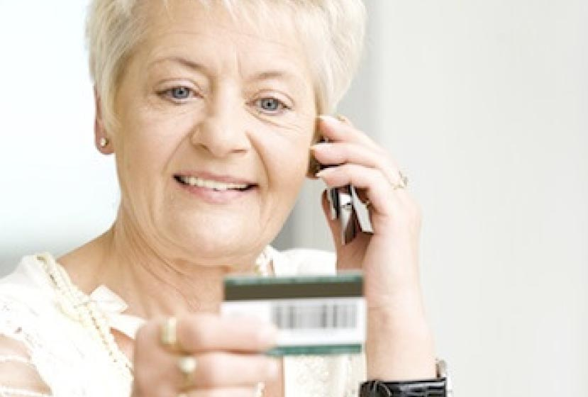 A woman looks at her credit card while on a phone call