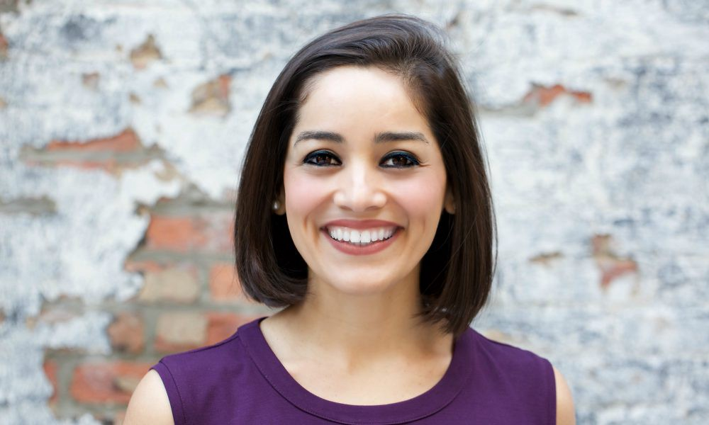 A smiling beautiful woman with short-length hair.