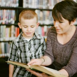 professora com aluno em concurso de leitura