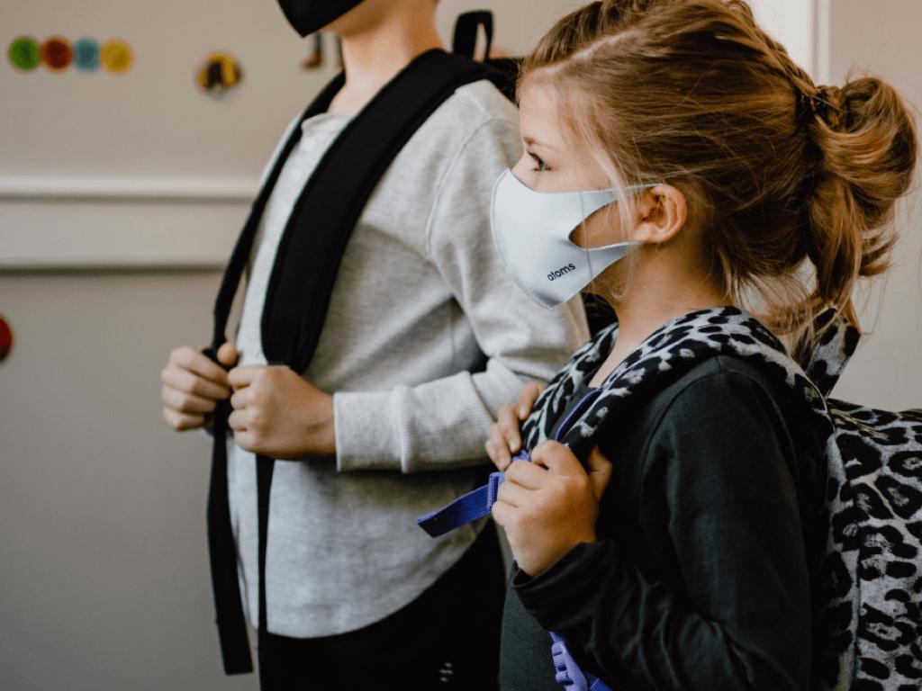crianças com máscara indo para escola