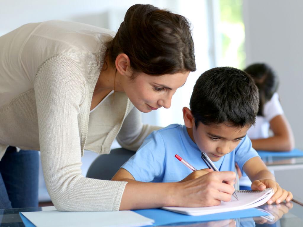 professora realizando avaliação qualitativa com aluno