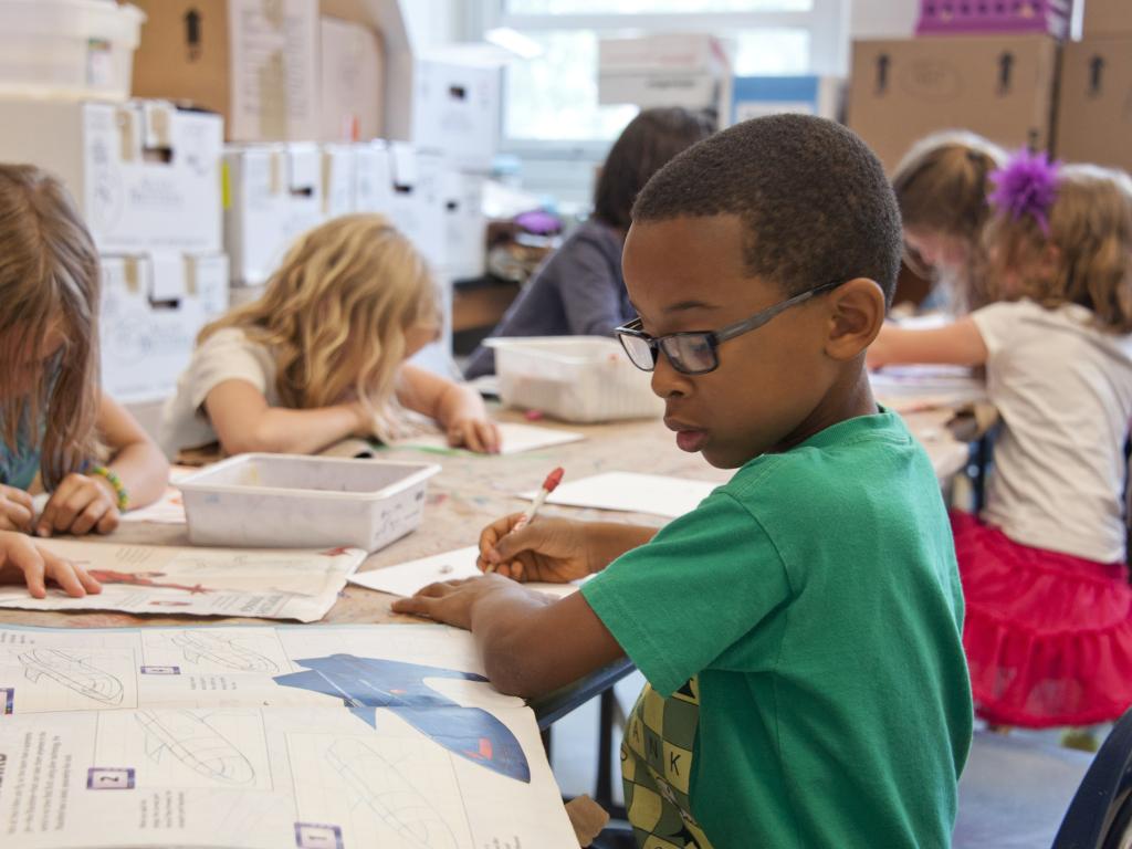 criança lendo livro na escola