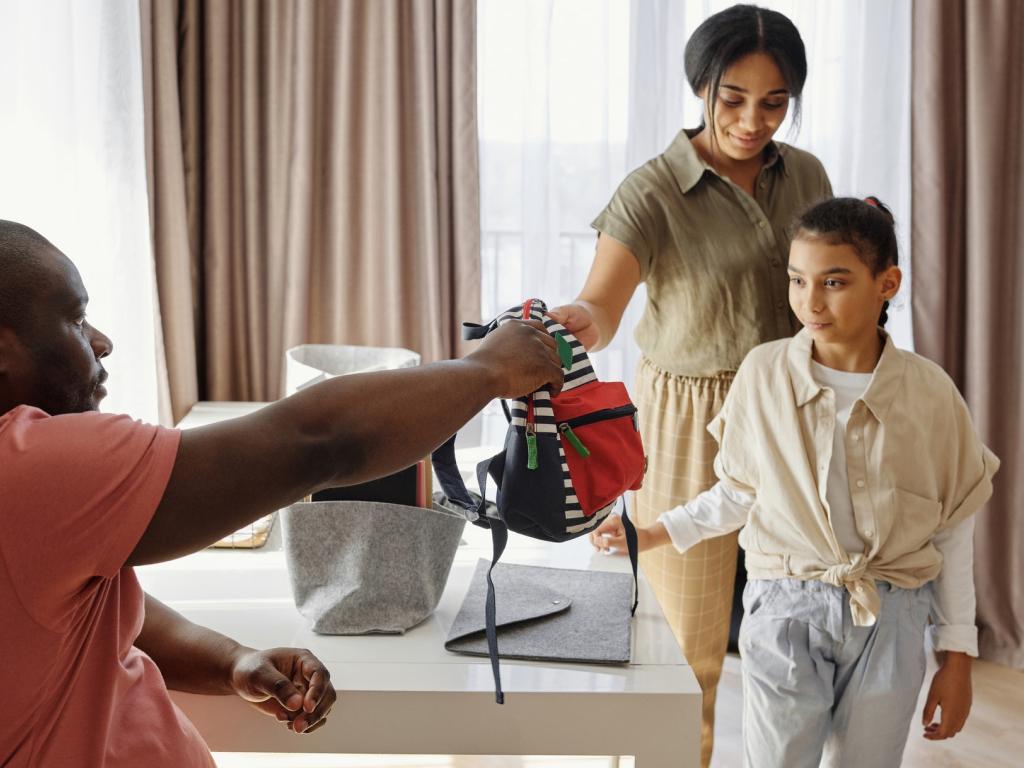 pai e mãe negros preparam filha negra para escola