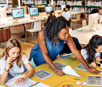 professora lendo com alunas