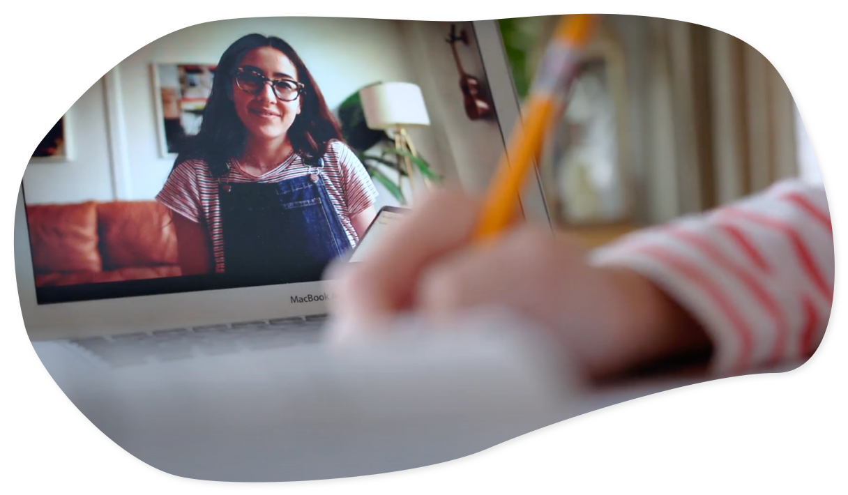A young girl writing while her learning partner is in the background on a video call