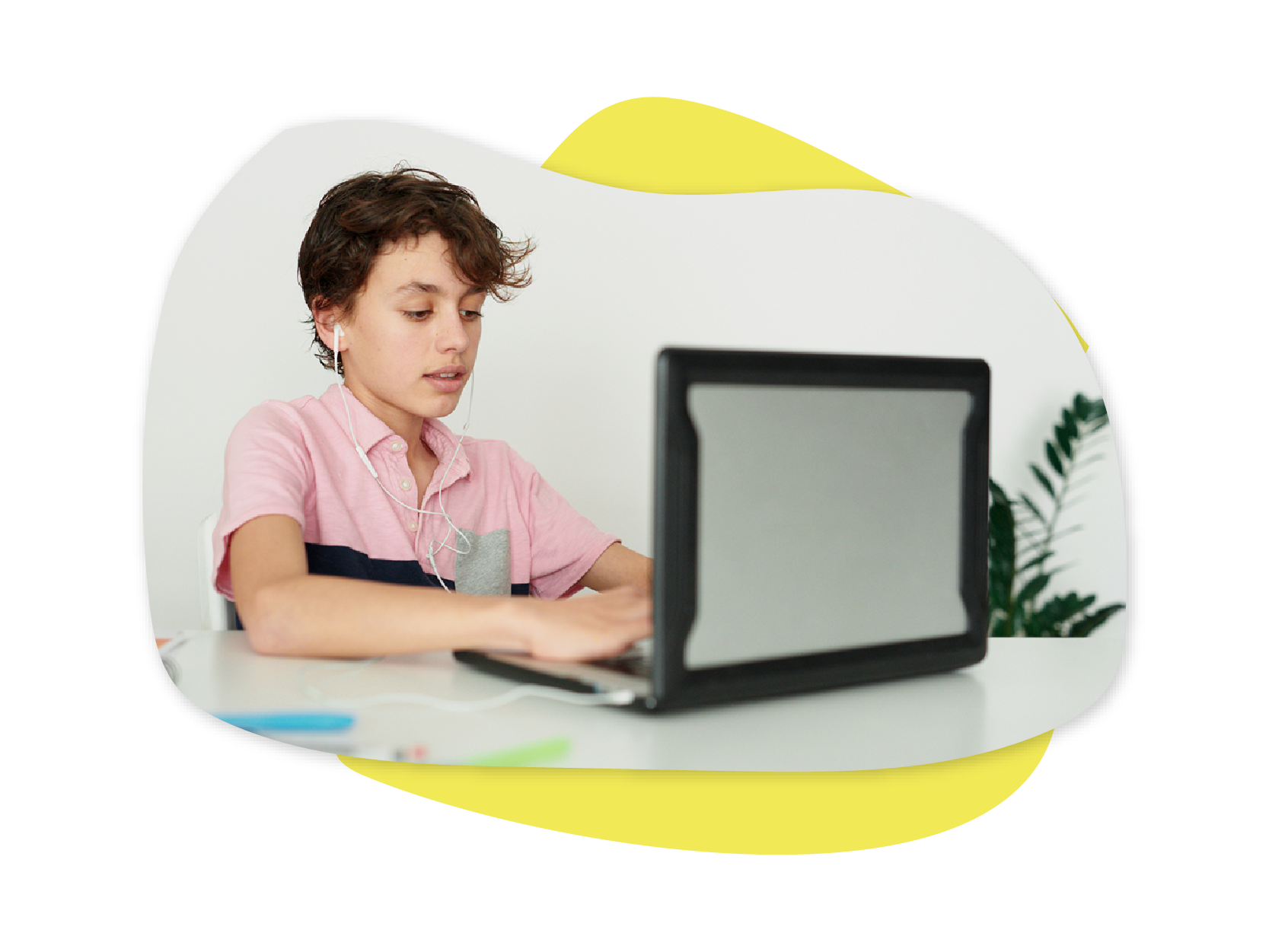 A Caucasian boy sitting at a desk and typing on a laptop
