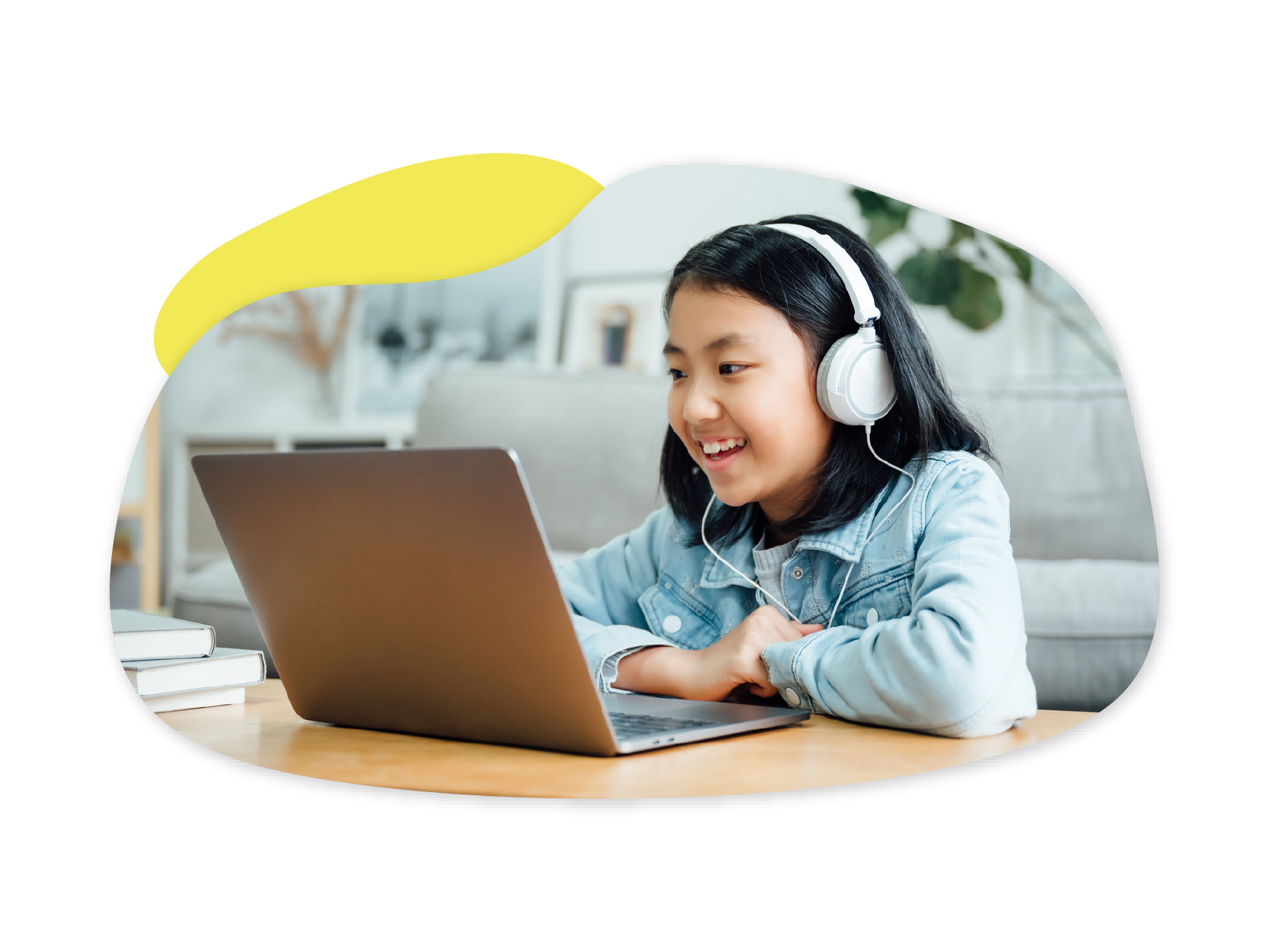 An Asian girl sits in front of a laptop while wearing headphones