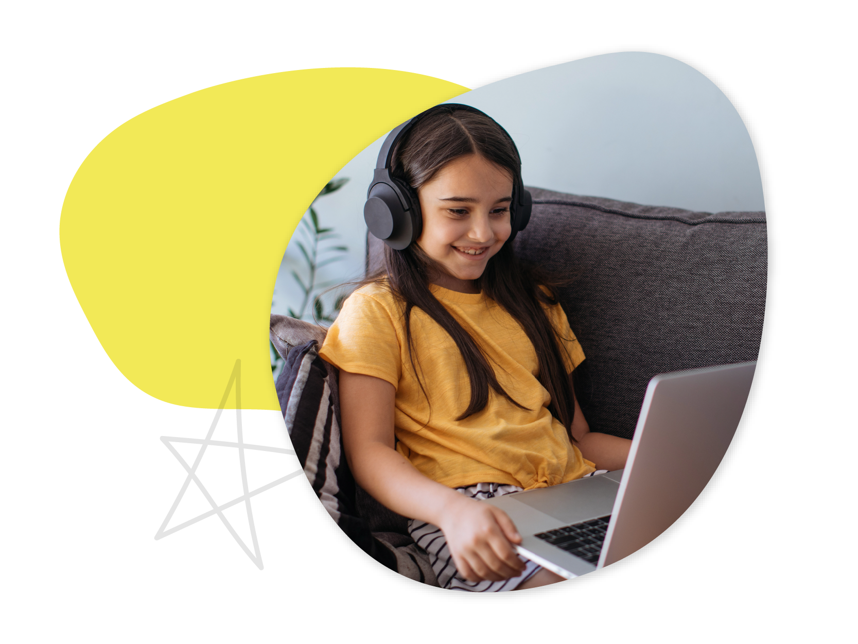 A young girl sits on a couch wearing headphones and holding a laptop