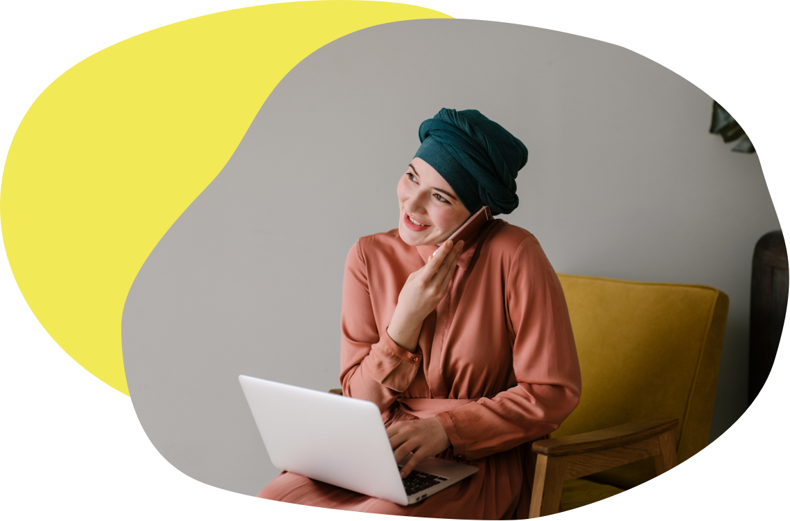 A woman wearing a headscarf talks into a phone while balancing a laptop