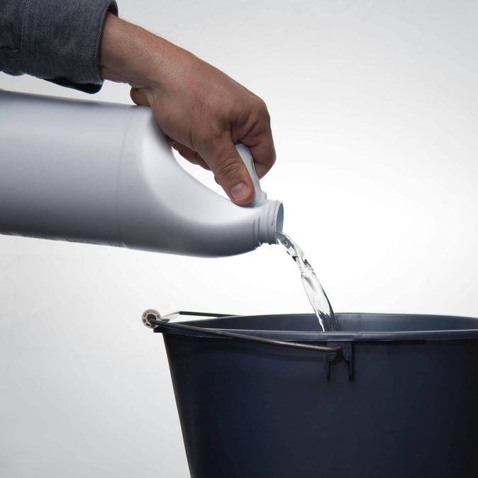 Person pouring bleach from a white container into a bucket [Unioncrate]