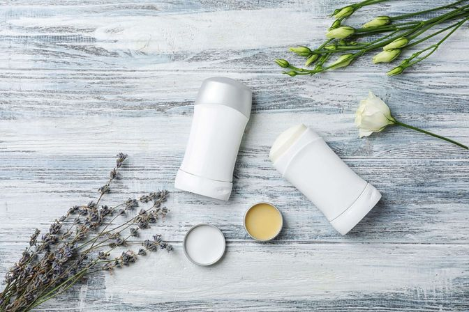 Sticks of deodorant on a table with flowers [Unioncrate]