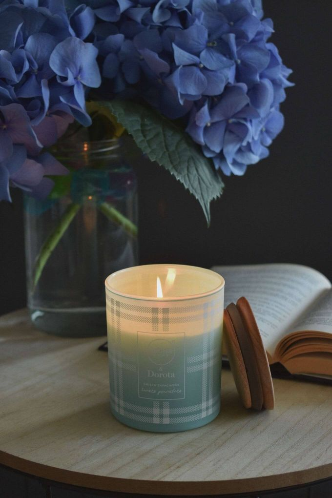A lit scented candle next to a vase of hydrangeas [Unioncrate]