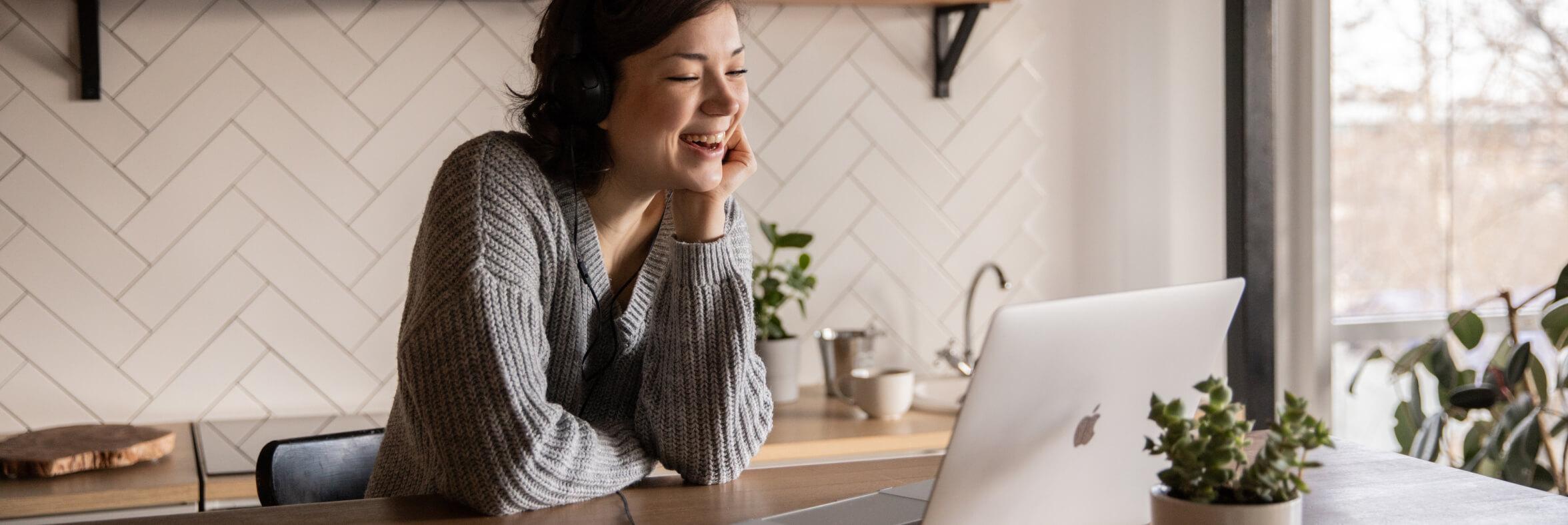 Woman laughing at computer