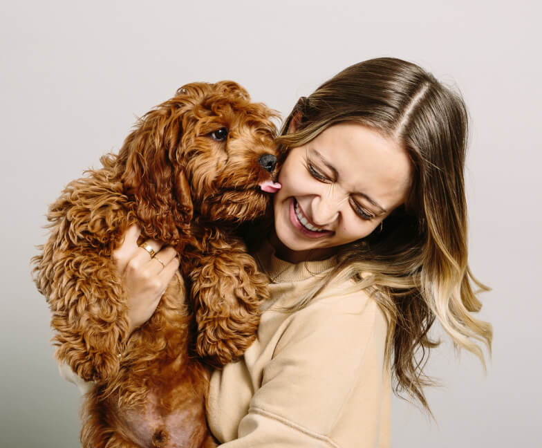 Women laughing while holding a puppy