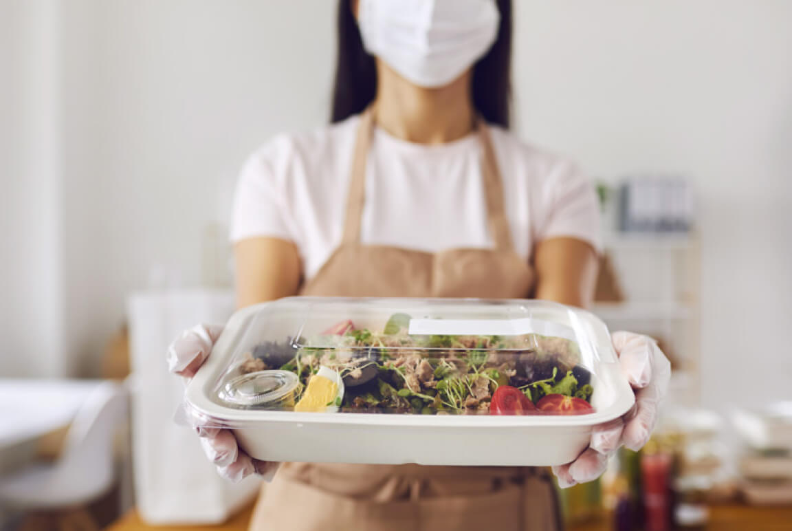 Woman in a mask and gloves serving an individually packaged meal