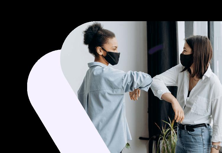 Two women in masks touching elbows
