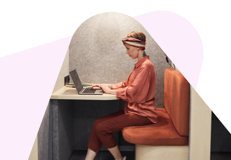 Woman sitting on computer in a booth