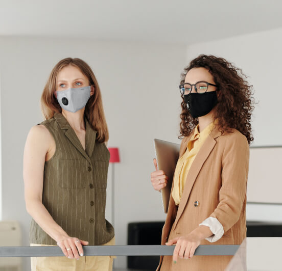 Two women standing together with masks on