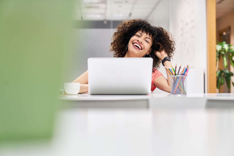 Woman at laptop, laughing