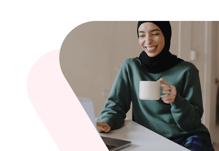 Woman smiling behind computer with coffee mug