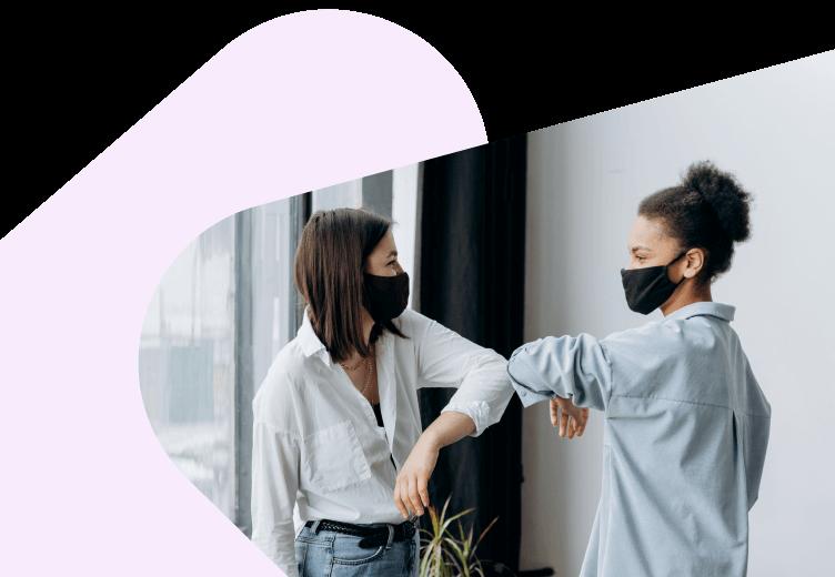 Two women touching elbows in masks
