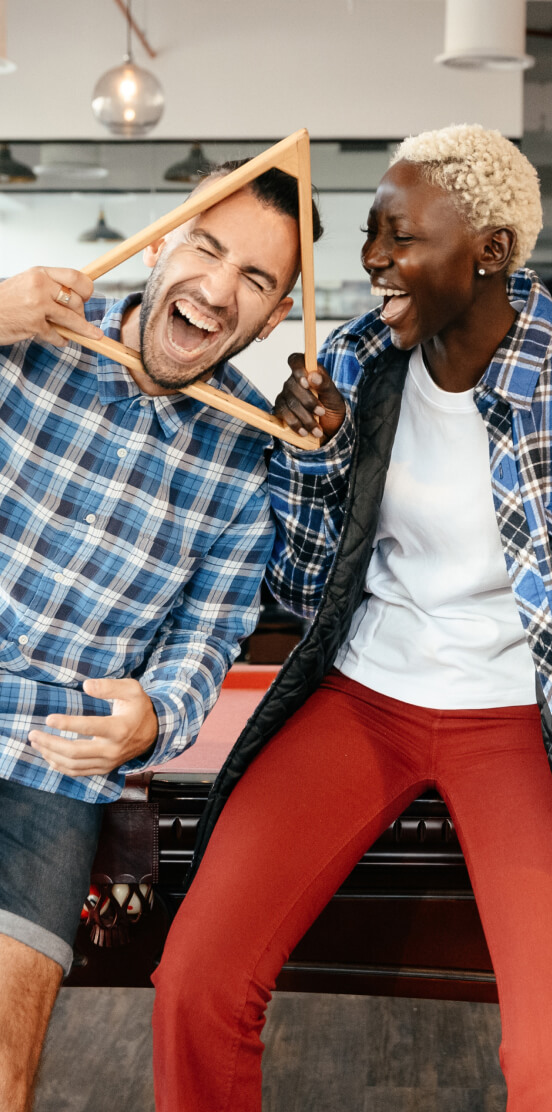 Two friends laughing while playing billiards