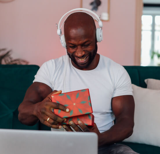 Person on a virtual meeting smiling while opening a gift box