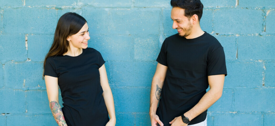 Two smiling people wearing casual black employee swag t-shirts