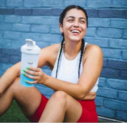 Smiling person in a training cloth drinking water from a tumbler cup and resting after a workout