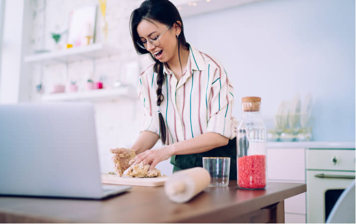Person kneading dough in the kitchen next to the laptop during the virtual cooking class